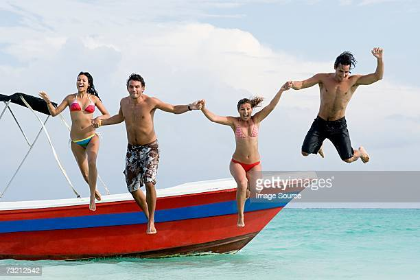 Friends jumping off boat