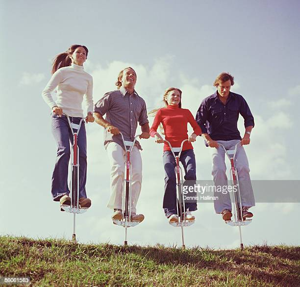 Friends jumping on pogo sticks