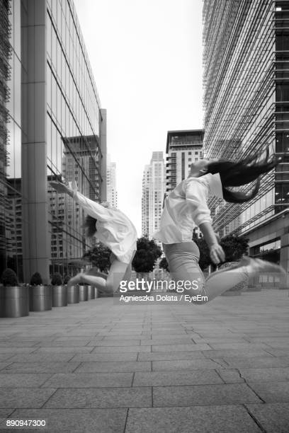 Friends Jumping On Street Amidst Buildings