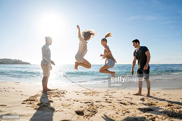 Friends jumping rope at the beach