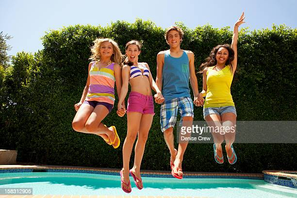 Friends jumping together near swimming pool