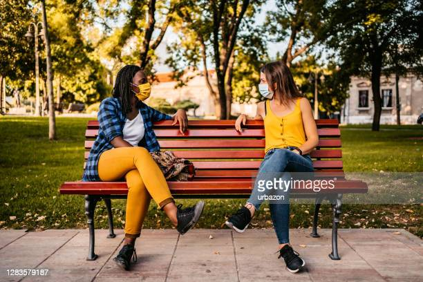 friends keeping social distance on bench - bench stock pictures, royalty-free photos & images