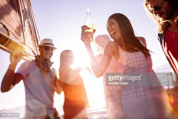 Friends laughing and dancing on a yacht at sunset
