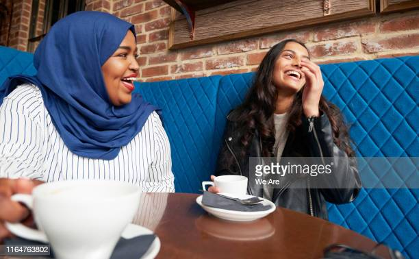 friends laughing and drinking coffee in a cafe - friendship stock pictures, royalty-free photos & images