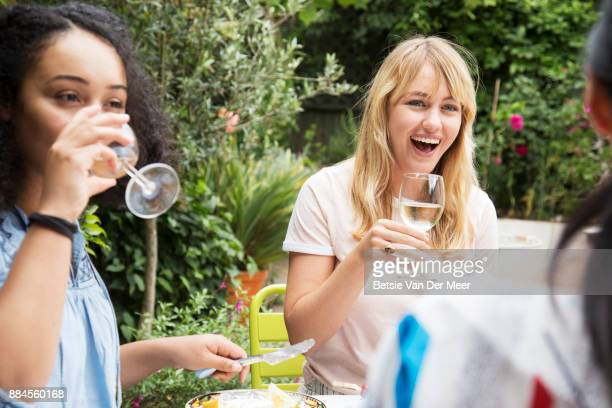 Friends laughing and drinking wine at dinnerparty in garden.