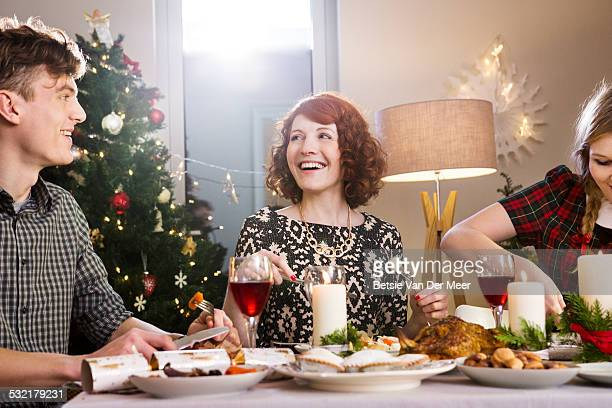 Friends laughing and eating Christmas dinner.