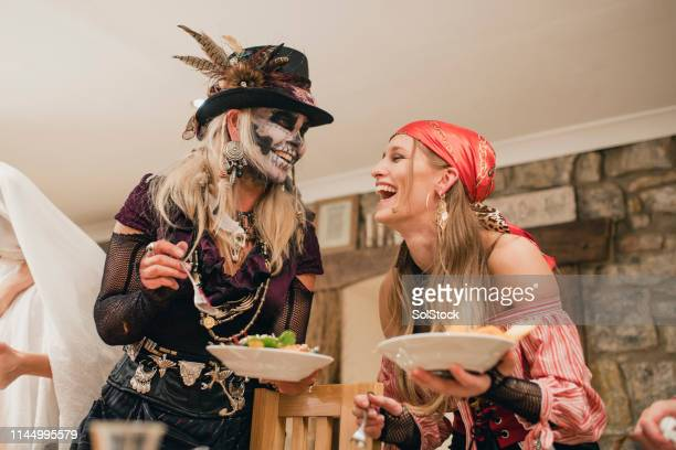 friends laughing and eating - halloween party stock photos and pictures
