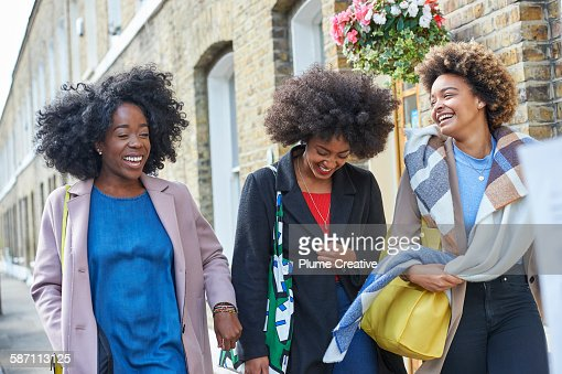 Friends laughing and walking down the street.