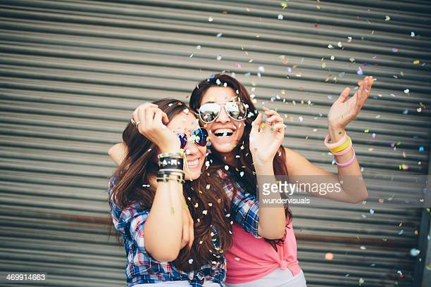 Friends laughing as confetti falls on them