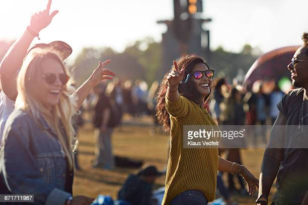friends laughing at big festival concert - incidental people stock pictures, royalty-free photos & images