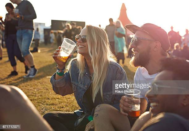 Friends laughing at big festival, holding beers