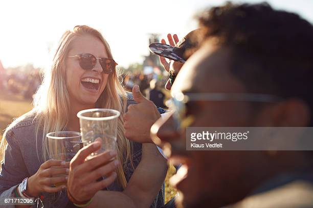 Friends laughing at big festival with beers