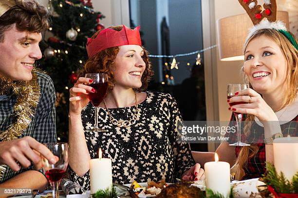 Friends laughing at Christmas dinner party.