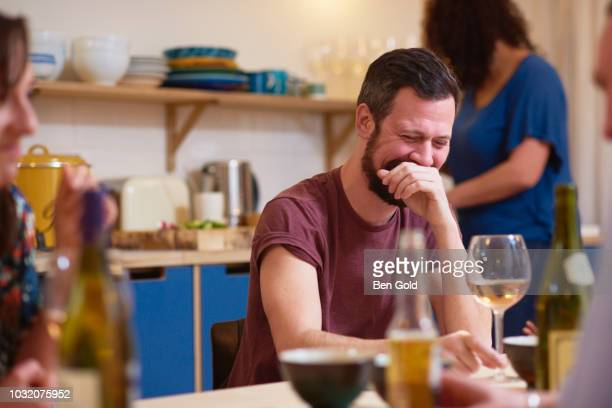 friends laughing at dinner party - hands covering mouth stock pictures, royalty-free photos & images