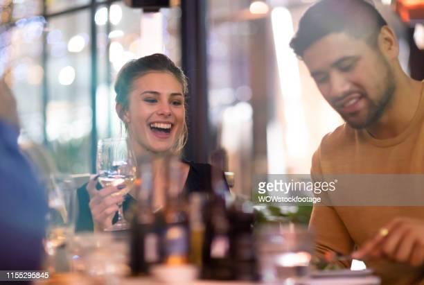 friends laughing at dinner - auckland photos et images de collection