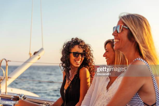 friends laughing during boat trip in the evening light - irony stock pictures, royalty-free photos & images