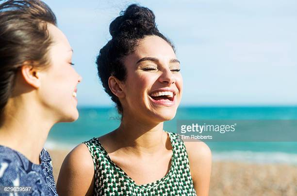 friends laughing on beach - young women stock pictures, royalty-free photos & images