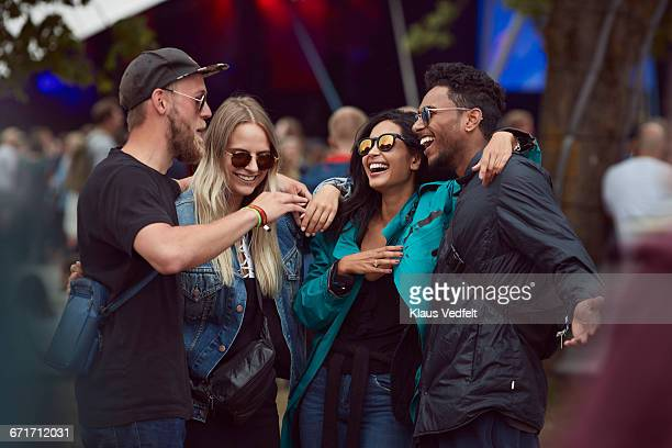Friends laughing together at outside festival