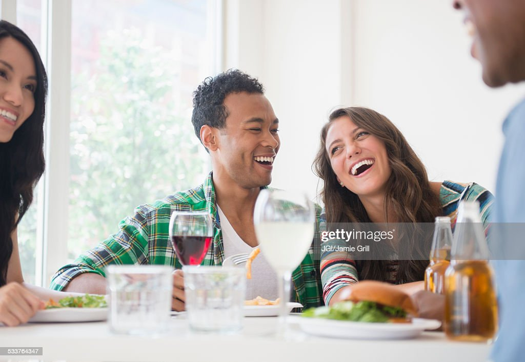 Friends laughing together at restaurant : Foto stock