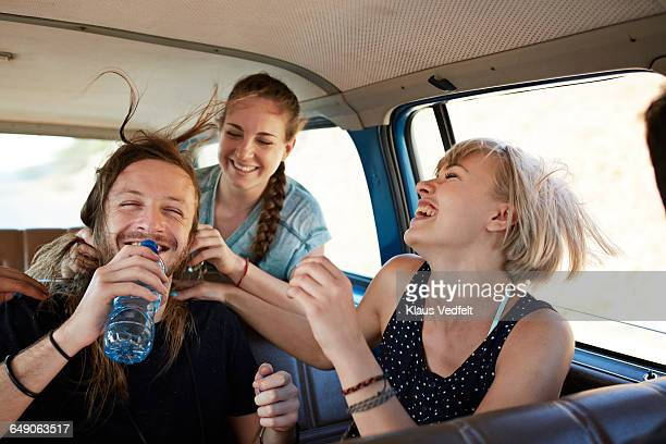 Friends laughing together inside car