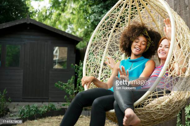friends laughing together on swing seat in garden - wicker stock pictures, royalty-free photos & images