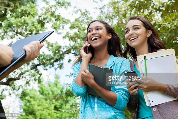 Friends laughing together outside on college campus