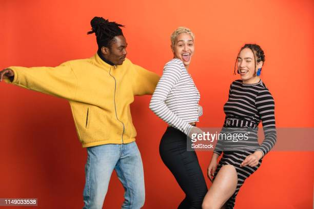 friends laughing together - orange background stock pictures, royalty-free photos & images