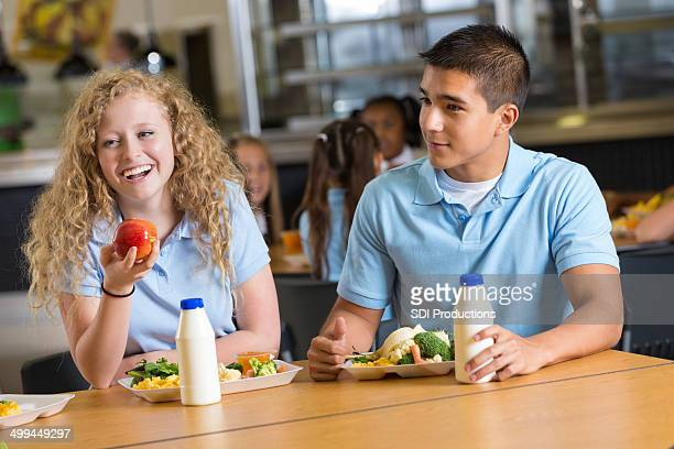 friends laughing together while eating in school cafeteria - kid girl eating apple stock photos and pictures