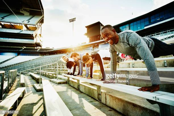 Friends laughing while doing pushups in stadium