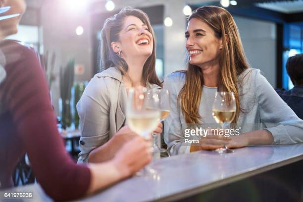 friends laughing while enjoying drinks in bar - white wine stock pictures, royalty-free photos & images