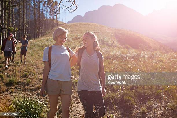 Friends laughing, while hiking down mountain