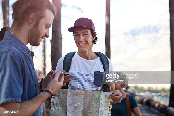 Friends laughing while holding map and compass