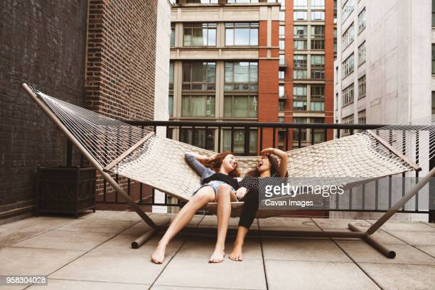 Friends laughing while lying on hammock in patio