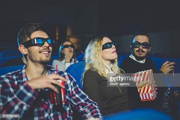 Friends laughing while watching a movie