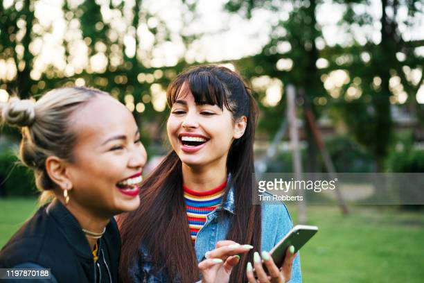 friends laughing with smart phone, city park - adults only photos stock pictures, royalty-free photos & images