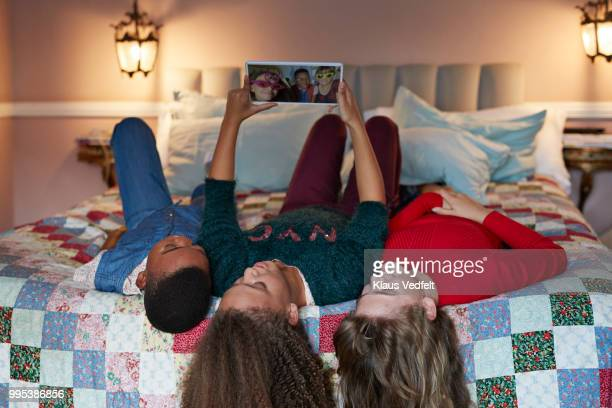 Friends laying in bed and looking at tablet with selfies