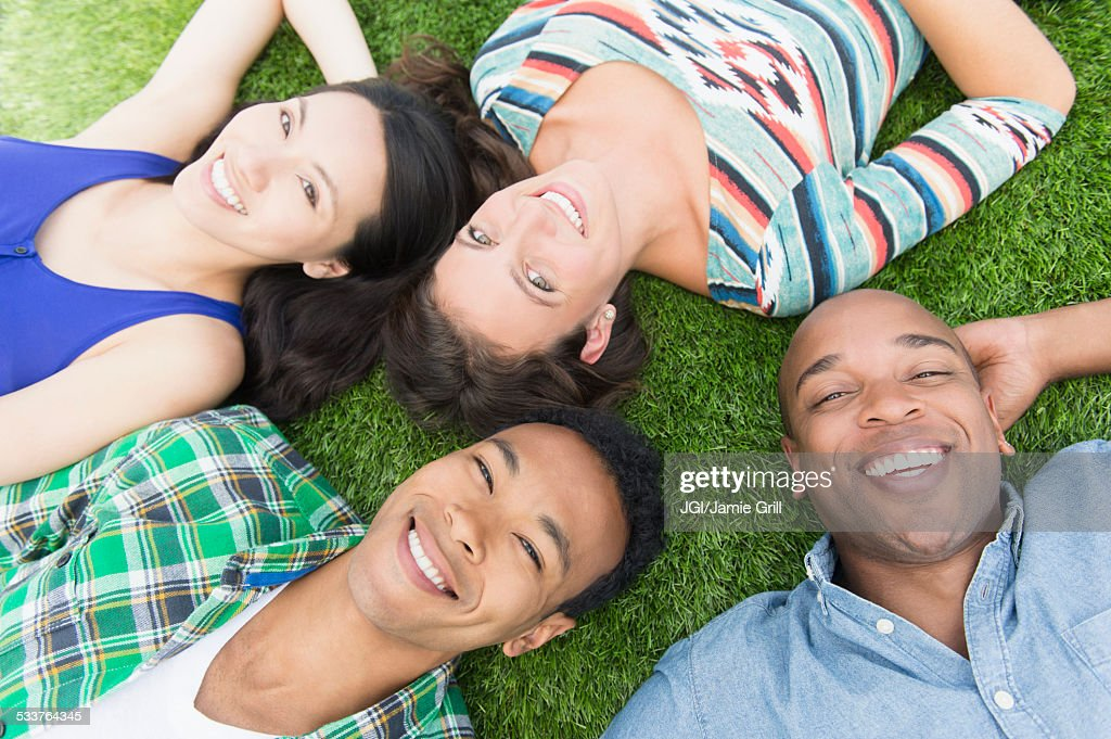 Friends laying in grass outdoors : Foto stock