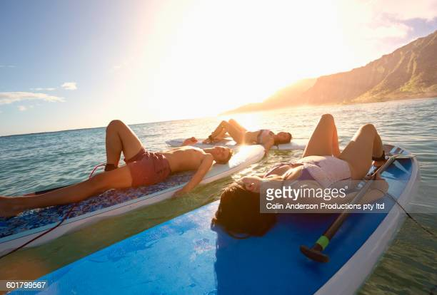 friends laying on paddle boards in ocean - waikiki stock pictures, royalty-free photos & images