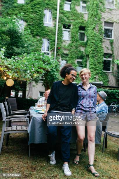 friends leaning on table after outdoor meal - middelgrote groep mensen stockfoto's en -beelden