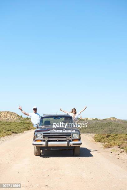 Friends leaning out of car window with hands in the air