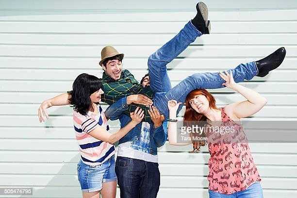 friends lifting man in air