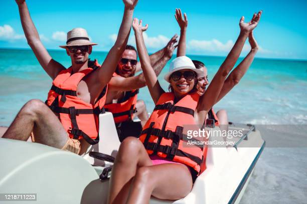 friends lifting their arms up during pedal boat fun on sea - pedal boat stock pictures, royalty-free photos & images