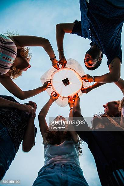 Friends lighting up a paper lantern at party