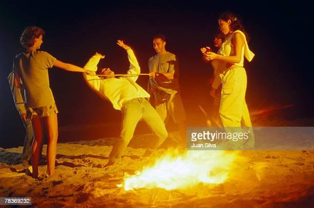 Friends limboing on beach at night