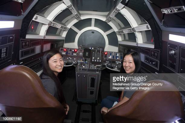 Friends Lindsay Yamauchi, left, and Karen Misaki, get ready to have their photo taken inside the life-size cockpit of the Millennium Falcon during...