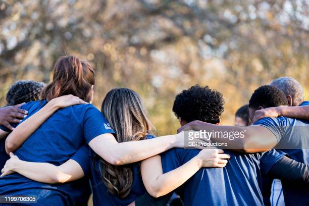 friends linking arms in unity - arm around stock pictures, royalty-free photos & images