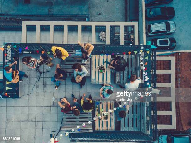 friends listening to a music band on the rooftop - roof stock photos and pictures