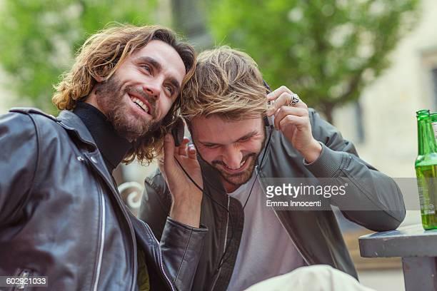 friends listening to music sharing headphones - レザージャケット ストックフォトと画像