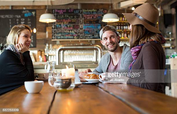 Friends listening to woman at coffee table