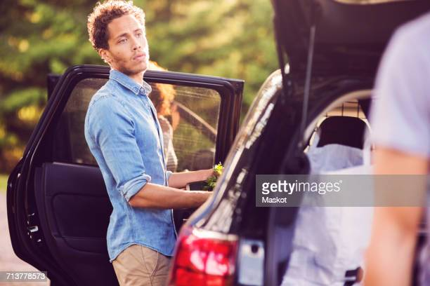 Friends loading luggage into car on sunny day